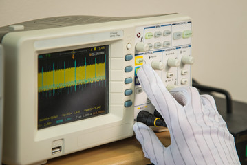 Modern oscilloscope, man's hand adjusting wave signals, closeup