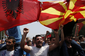 Anti-government protesters wave Albanian and Macedonian flags during a demonstration in Skopje