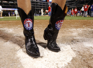 A woman wears cowboy boots with the Texas Rangers logo as the team celebrates on the field after advancing to the World Series by eliminating the Detroit Tigers in Game 6 of MLB's ALCS baseball playoffs in Arlington