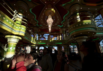 Tourists take pictures of a ballroom in a building designed by Aymara architect Freddy Mamani, in El Alto city on the outskirts of La Paz