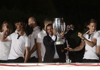 Atletico Madrid's coach Sanchez Flores lifts the European Super Cup soccer trophy next to players during the celebrations of their victory in Madrid