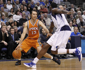 Suns guard Nash looks to drive on Mavericks center Mahinmi during their NBA basketball game in Dallas, Texas
