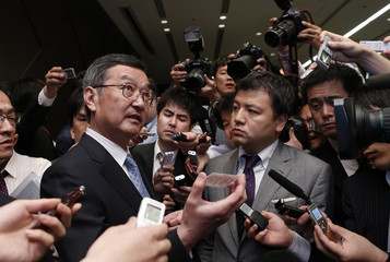 Sharp Corp's Representative Director and Executive Vice President Kozo Takahashi is surrounded by media personnel at a news conference in Tokyo