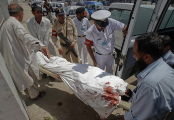 Hospital workers and naval security officials move the body of a bomb blast victim to a hospital morgue in Karachi