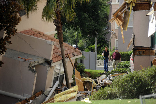 Workers inspect a section of the Summer Bay Resort after a large sinkhole opened on the property's grounds, in Clermont, Florida