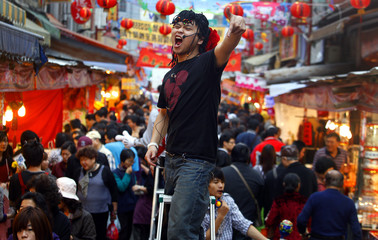 A man shouts special offers for food products to people visiting the Dihua Chinese Lunar New Year street market in Taipei