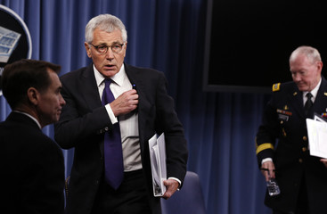U.S. Secretary of Defense Chuck Hagel and Chairman of the Joint Chiefs of Staff Gen. Martin Dempsey leave after a press briefing at the Pentagon in Washington