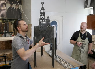 Ukrainian artists assemble a barbecue grill in the shape of Moscow's Kremlin at their workshop in Kiev