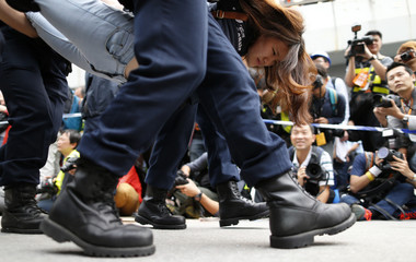 A demonstrator is taken away by police from an area previously blocked by pro-democracy supporters, outside the government headquarters in Hong Kong