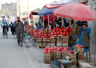 An Afghan man sells pomegranates along a street in Kabul