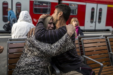 Ihab, 30, a Syrian migrant from Deir al-Zor, cries as he hugs his mother Huda, 48, as he and his family arrive at railway station in Lubeck