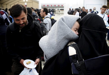 Migrants receive sweets during celebrations for Eid-al-Adha at a transit camp in Gevgelija