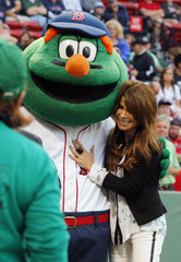 "Entertainer Paula Abdul hugs Boston Red Sox mascot ""Wally the Green Monster"" before the MLB Interleague baseball game between the Nationals and the Red Sox at Fenway Park in Boston"