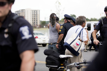 A protester is detained by the police during a march outside the site of the Democratic National Convention in Charlotte