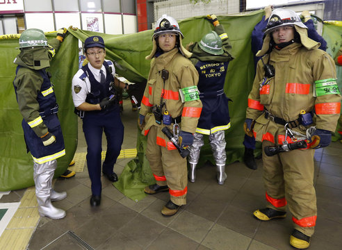 Firefighters hold a canvas sheet at the Hogo Sanchome station where an explosion is reported in Tokyo