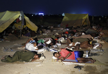 Ethiopian migrants sleep out in the open near a transit centre where they wait to be repatriated, in Haradh