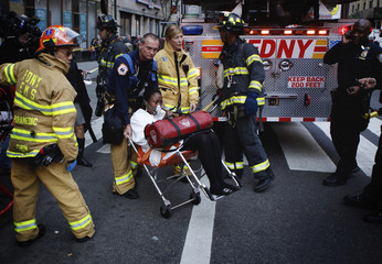 A woman is escorted by New York Fire Department personnel after being overcome by fumes in a midtown Manhattan office building in New York