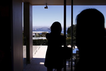 Bao Fang, a potential buyer from Shanghai in China, takes a photograph of the Sydney Opera House and Harbour Bridge as real estate agent LuLu Sun escorts her around a property for sale in the Sydney suburb of Vaucluse, Australia
