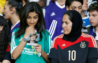 """International female soccer players of the """"Discover Football"""" project read autograph cards of German Chancellor Merkel before a group picture at the chancellery in Berlin"""