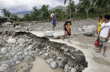 Residents walk along a destroyed road towards an evacuation centre after typhoon Bopha hit in Compostela Valley, southern Philippines