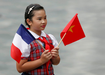 A Vietnamese school girl holds Vietnamese and French flags while she waits for the arrival of France's President Francois Hollande at the Presidential Palace in Hanoi, Vietnam
