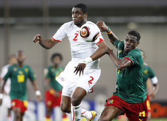 Cameroon's Idrissou and Tunisia's Souissi chase the ball during an African Nations Cup soccer match in Lubango