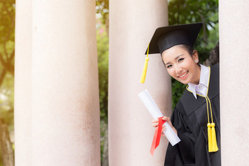 Beautiful graduate girl in gown smile with certificated in hands and looks up