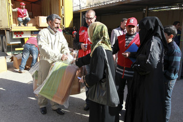 Syria's refugees living in Jordan receive humanitarian supplies from the Red Crescent organization in Amman