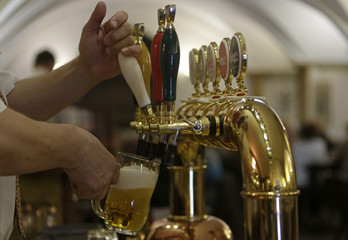 A bartender drafts a glass of beer from a tap at Budejovicky Budvar (Budweiser Budvar) brewery in Ceske Budejovice