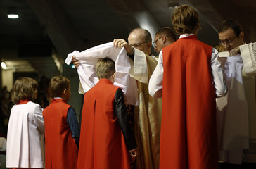 A priest inaugurates new altar boys during a Mass at the Temple of Divine Providence in Warsaw