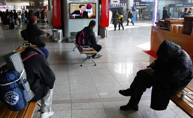 People are seated in front of a live television broadcast of South Korean President Lee Myung-bak speaking in a talk show at a railroad station in Seoul