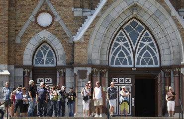 People stand on the stairs of Sainte-Agnes Church to view devastation from derailment in town of Lac-Megantic