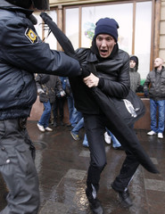 A policeman detains an activist during a rally to protest against violations at the parliamentary elections in St. Petersburg