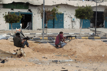 Anti-Gaddafi fighters return fire during clashes with Gaddafi forces in Sirte in the center of Sirte