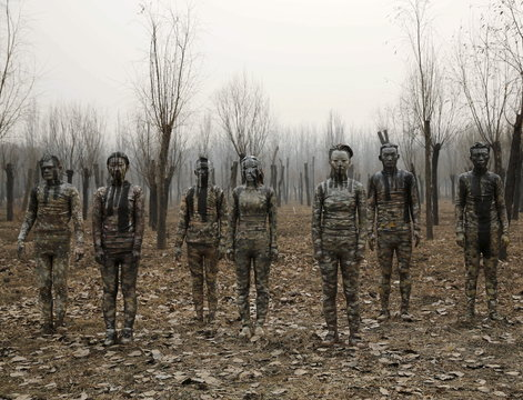 """Models painted in camouflage colours to blend in with the background pose for Chinese artist Liu Bolin's artwork """"Dongji"""", or Winter Solstice, in Beijing"""