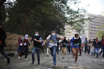 Anti-Mursi protesters run for cover during clashes with riot police at Tahrir square in Cairo