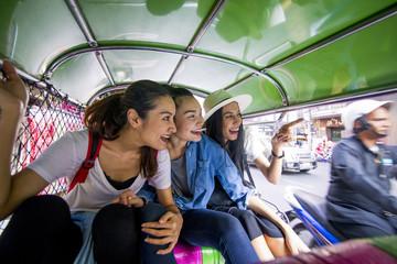 Three asian girls are exploring Chinatown, Thailand by Tuk tuk