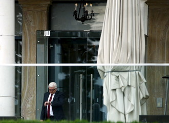 German Foreign Minister Steinmeier checks his watch outside the Beau Rivage Palace Hotel during a break in the Iran nuclear program talks in Lausanne