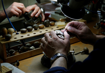 A staff sets precious stones into a watch part at independent watch industry supplier Horlyne in Le Locle