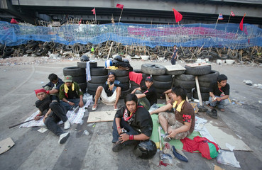 Anti-government 'red shirt' protesters sit behind a stack of tyres inside their barricade, built with bamboo poles and tyres, in the Silom business district in Bangkok