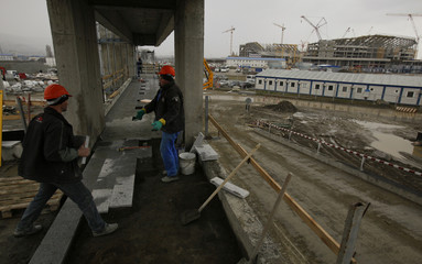 "Workers prepare a path to the Olympic stadium ""Fisht"" in Sochi"