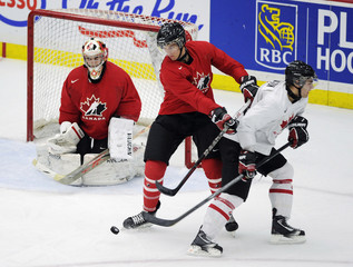 Canada's Team Red Alex Petrovic blocks a shot while pushing Team White Freddie Hamilton out from goalie Louis Domingue during their inter-squad game in Calgary