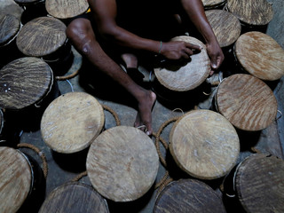 A man scrapes an animal skin on traditional drums at a workshop in Nittambuwa, Sri Lanka