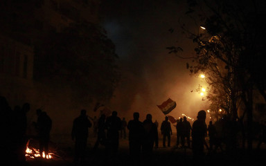Protesters wave flags during clashes with security forces in Cairo