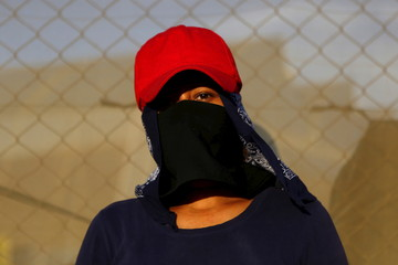 A farmworker poses for a photo with a handkerchief tied around his face to shield him against the sun and pesticide sprayed on fruits and vegetables in the farms, at Las casitas neighborhood in San Quintin in Baja California state