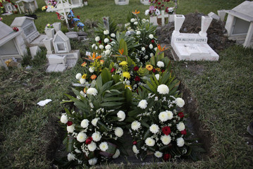 Flowers arrangements are seen on the grave of Colombian national Perez, a member of the Kombo Kolombia band, at La Piedad cemetery in the municipality of Juarez