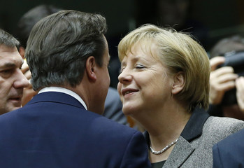 Britain's PM Cameron greets Germany's Chancellor Merkel during a EU leaders summit in Brussels