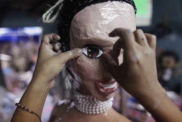 Adriana Ramirez puts fake eyelashes on a pinata depicting TV celebrity Kim Kardashian at her brother's workshop in Reynosa