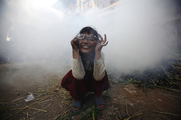 A girl rubs her eyes as smoke rises from a burning effigy of the demon Ghantakarna, symbolizing the destruction of evil, during the Ghantakarna festival at Bhaktapur