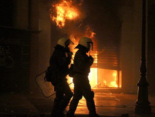 Riot police walk past burning building during violent protests in central Athens